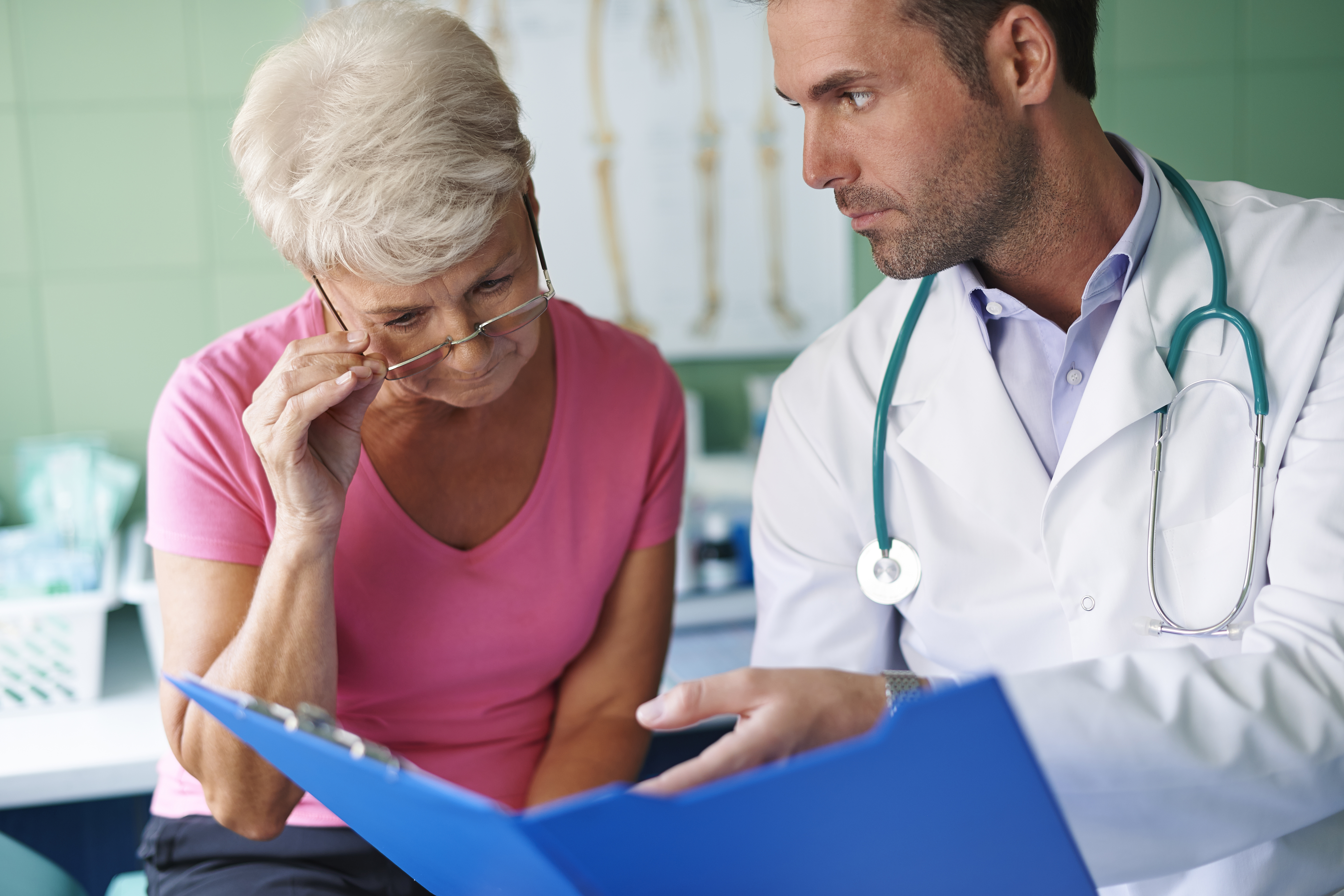 Dr. showing medical records to senior female patient